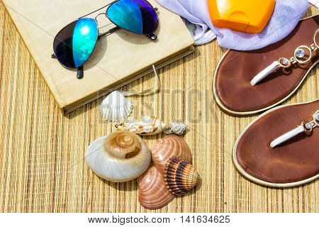 Beach accessories-Straw hat sarong sun glasses and flip flops on a beach