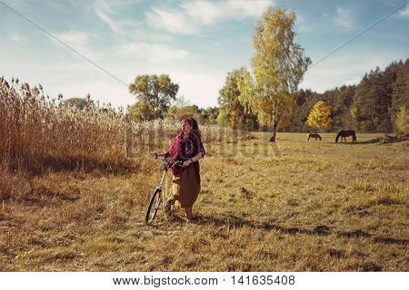 Beautiful young woman in long skirt and wool scarf riding retro style bicycle in field. Outside shot. Autumn season. Copy space.