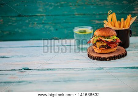 Tasty street food grilled beef burger in crispy shortbread with lettuce and mayonnaise served on small cutting board a rustic wooden table with copy space