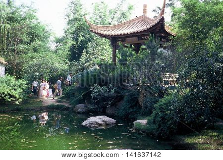 GUANGZHOU / CHINA - CIRCA 1987: People approach a pavilion near a pond in the Canton Orchid Garden in Guangzhou.