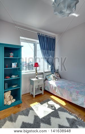 Children's bedroom with white walls and a parquet with carpet on the floor. There is a bed with colorful veil and pillows and a toy, turquoise bookcase with toys and books, nightstand with a lamp.