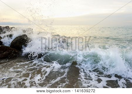 Ocean slash spray is a sunset seascape with rocks near the shore as a breaking wave sprays up in the air.