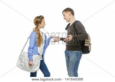 Beautiful teenage girl and boy in casual clothes with school bags standing over white background. Talking students. Isolated. Copy space.