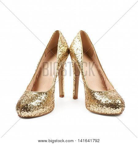 Pair of shining golden high-heeled footwear shoes, composition isolated over the white background