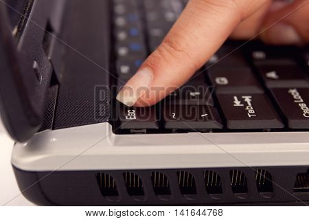 females finger pressing escape button on keyboard