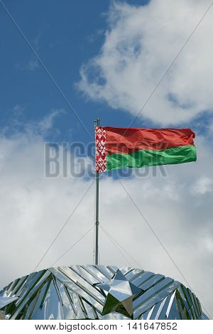photographed closeup of the flag of Belarus. blue sky. ragged old flag