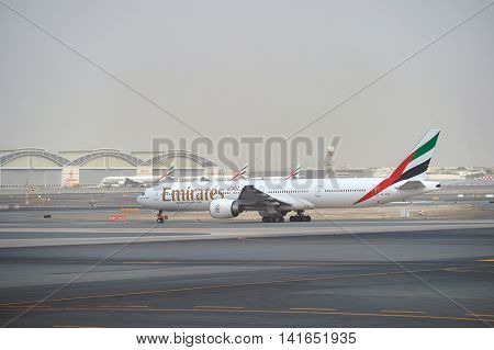 DUBAI, UAE - MARCH 10, 2015: Emirates Boeing 777 at Dubai International Airport. The Boeing 777 is a family of long-range wide-body twin-engine jet airliners.