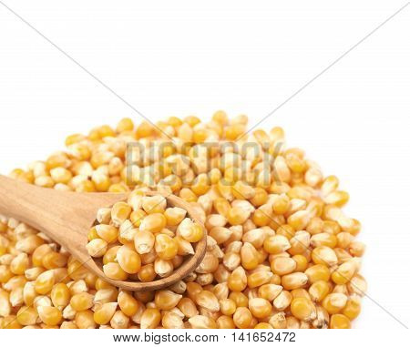 Pile of corn kernels with a serving wooden spoon over it, close-up crop composition isolated over the white background