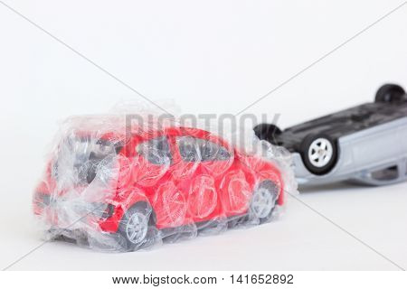 horizontal photo of two cars toy in accident scene. The safe red one is protected with air bubble on blank background.