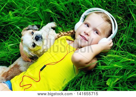 happy girl with a dog listening to the music on a summer day