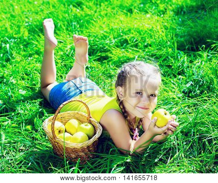 happy girl eating apples in the park