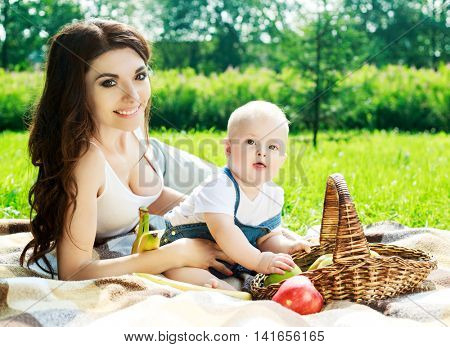mother and her baby having a picnic in the summer park