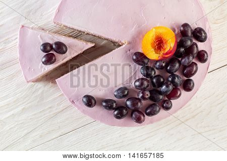 Cut piece fruit cheesecake decorated with grapes. Top view