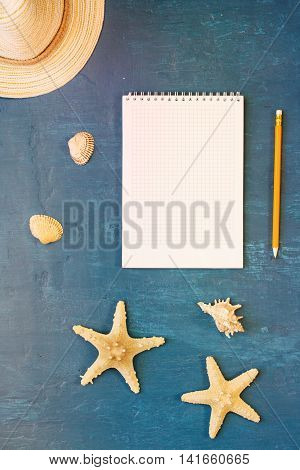 Notepad with blank page with pencil straw hat shells and starfish on blue surface top view. Summer background