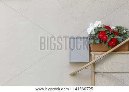 Fragment of a wall by entrance to the house with flower pots and postbox. Copy space for text