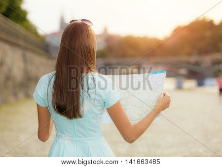Female tourist with map visiting city, photography from behind, old town center on background