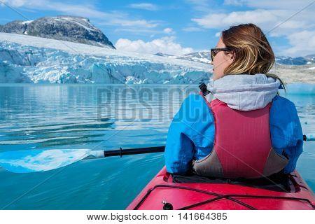 Woman kayaking on Styggvatnet glacier lake near Jostedalsbreen glacier. Norway.