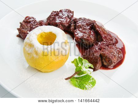 Restaurant food - chicken liver in pomegranate sauce with baked apple isolated on white background, closeup