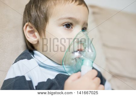 Baby boy with asthma problems making inhalation with mask on her face