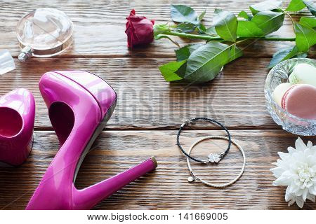 Female accessories on wooden background with sweets and flowers. Top view on messy woman boudoir
