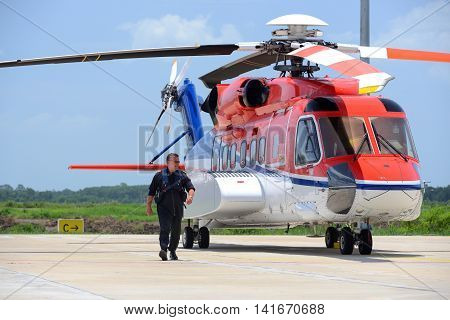 offshore helicopter pilot is walking and smiling beside of S92 helicopter at apron