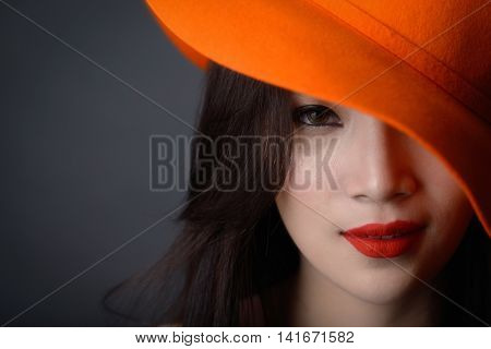 Portrait of beautiful asian woman model in orange striped hat with red lips