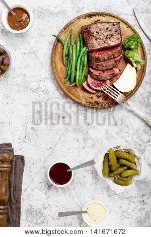 Rare steak with side dish of French beans and broccoli on wooden board top view