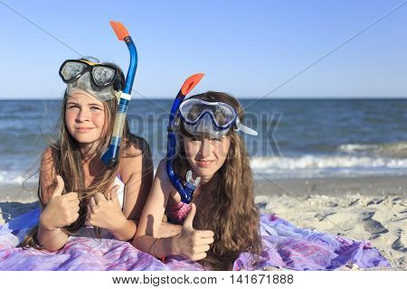 Girls on the beach in summer with a mask and tube for scuba diving.