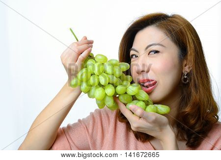 A beautiful asian woman with green grape