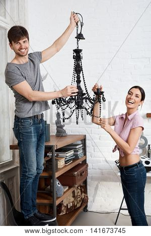 Happy young couple holding new chandelier at home, having fun.