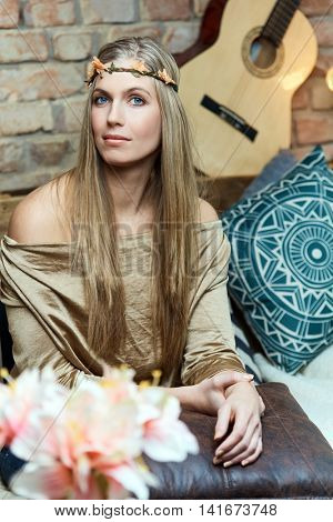 Attractive young hippy girl sitting at home wearing hair wreath.