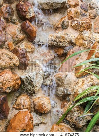 small water stream flowing over brown pebbles