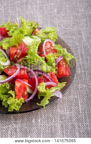 Fragment of a transparent plate with a fresh salad of raw vegetables closeup on a gray mat tabletop