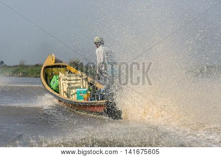 Sales man in a motorboat water spray for fast sail boat in Inle Lake. Myanmar. Burma.