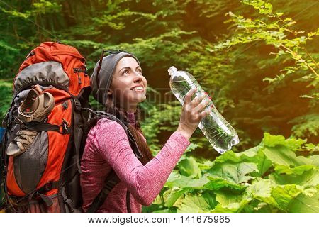 Hiker girl drinking water. Happy woman tourist with backpack drinking water in nature. Young tourist woman drinking water outdoor forest with sunshine in the background. Young woman with water bottle