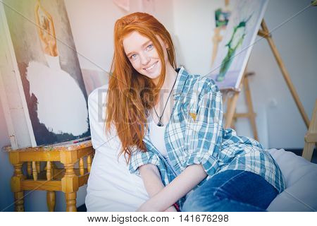 Attractive happy young woman with long red hair in checkered shirt and jeans sitting on soft white beanbag in art workshop