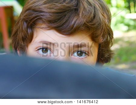 preteen handsome boy close up portrait behind the bicycle tire wheel