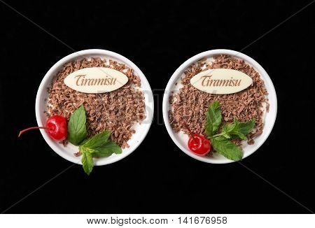 Tiramisu dessert on black background top view with chocolate decorated by cherry and mint