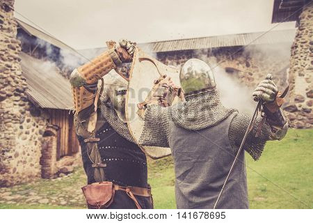 Fight between two medieval knights close to medieval castle
