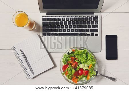 Healthy business lunch in the office, top view of vegetable salad on white wooden desk near laptop computer keyboard. Salad bowl, juice, mobile phone and notepad with pen flat lay. Snack at break time
