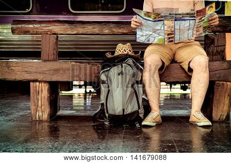 Young man traveler sitting with backpack look searching location map at the train station Travel concept soft focus vintage tone