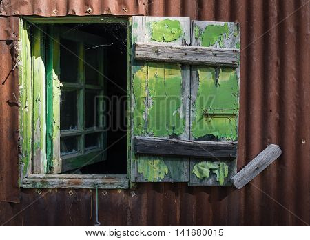 Open broken green wooden window on a metal brown wall from an abandoned deserted house.