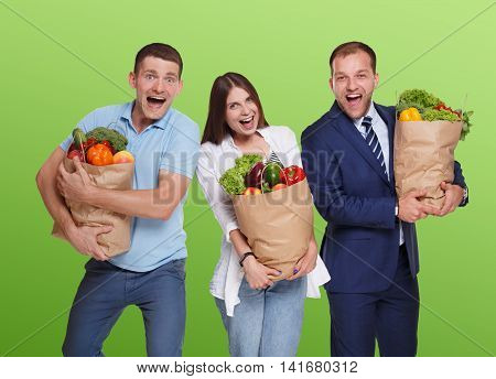 Happy people, two men and young woman hold shopping paper bags full of groceries, vegetables and fruits isolated at green background. Healthy food shopping, excited buyers