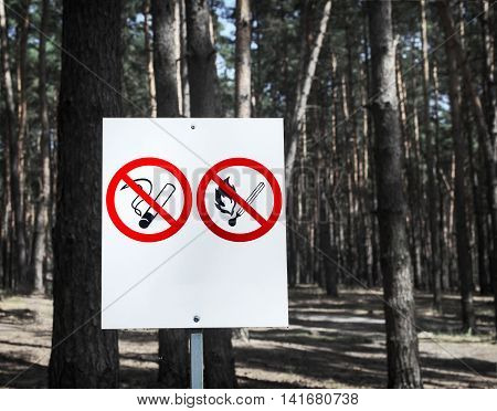 No Smoking and No Fire signs on a whiteboard in the forest.