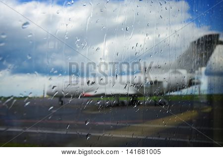 Abstract defocused photo of airplane at airport through the window with drops of rain. Focus on raindrops.