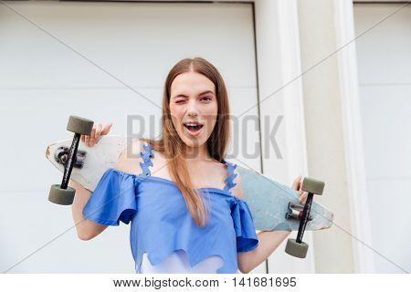 Young girl standing with skateboard and winking outdoors over white wall background