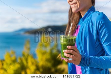 Healthy diet health conscious woman happy smiling drinking fresh green vegetable smoothie as a detox morning breakfast in beautiful autumn sun nature outdoors. View of ocean and mountains.