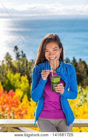 Healthy food living clean eating woman drinking fresh spinach vegetable smoothie in beautiful outdoors autumn nature at resort travel lodge with ocean view. Happy Asian girl fitness life.
