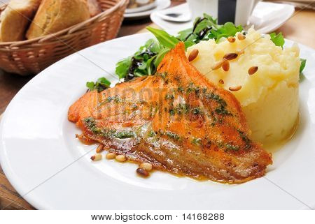 grilled salmon and lemon - french cuisine dish with fresh salad and salmon