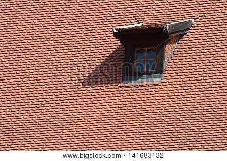 Mansard window in old tiled roof close up